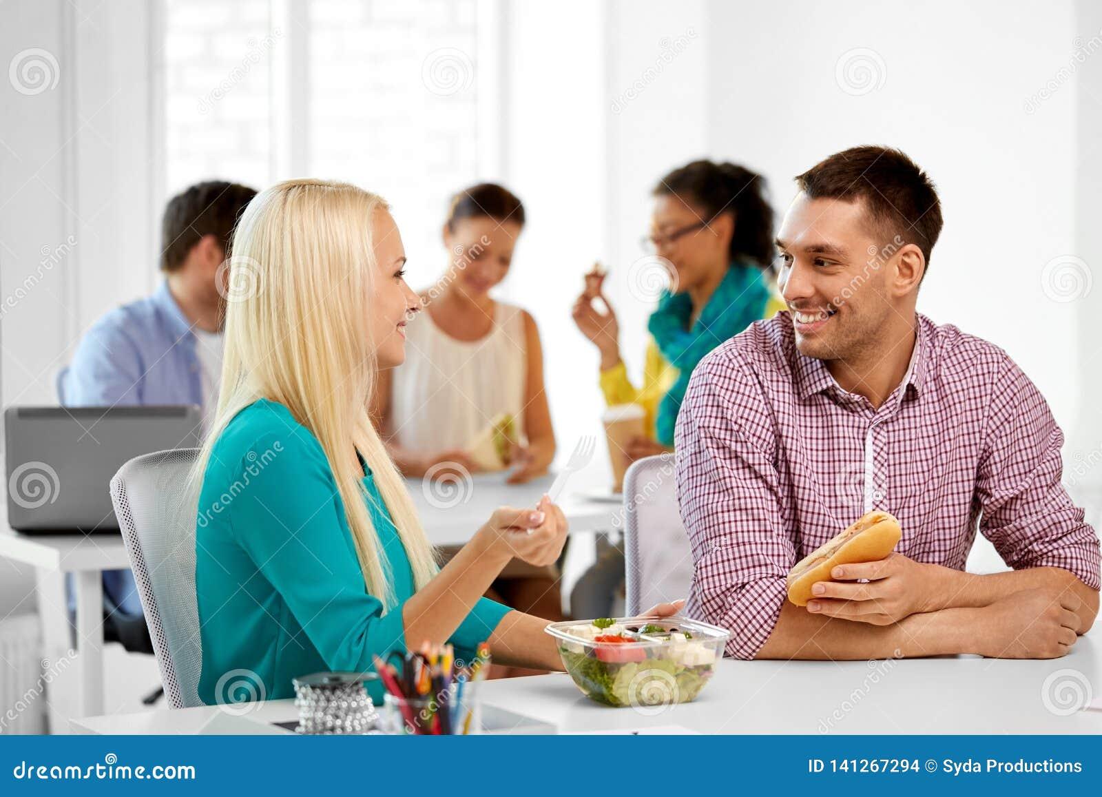 Glückliche Kollegen, die zu Mittag essen und im Büro essen