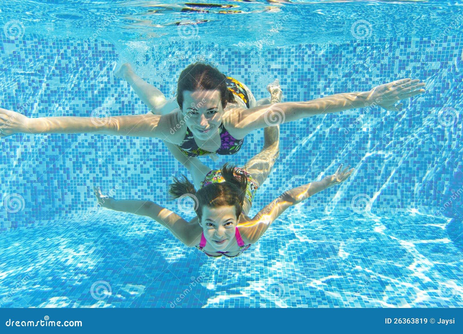 Glückliche lächelnde Familie underwater im Swimmingpool