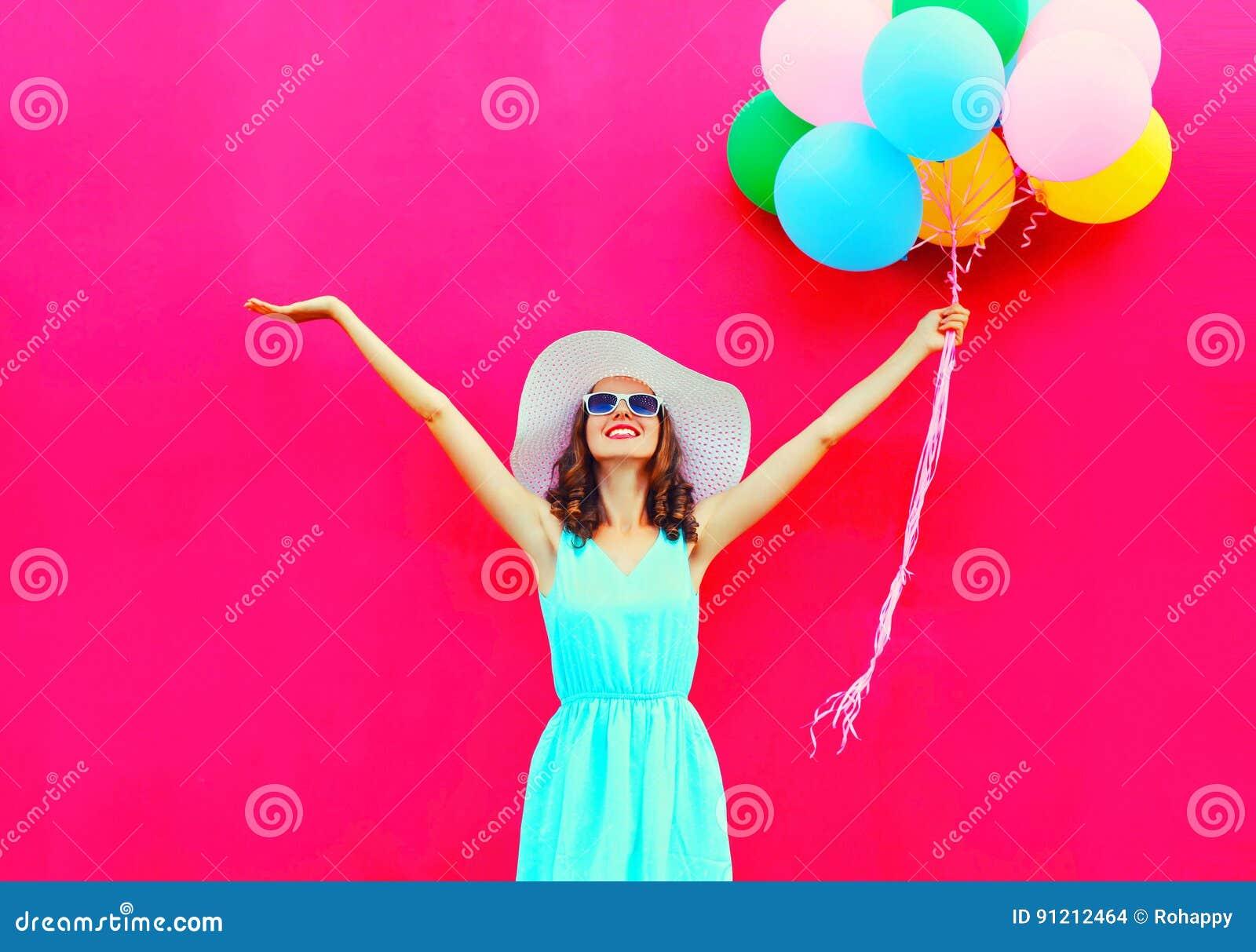 Glückliche lächelnde Frau der Mode mit bunten Ballonen einer Luft hat Spaß im Sommer über einem rosa Hintergrund