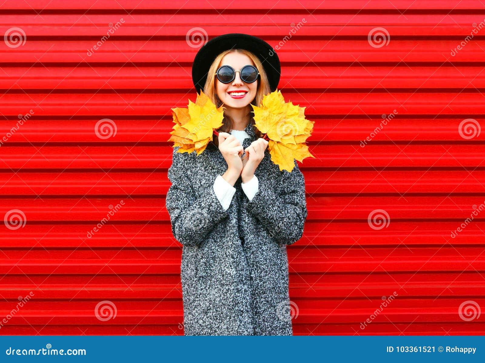 Glückliche lächelnde Frau des Modeherbstes hält gelbe Ahornblätter