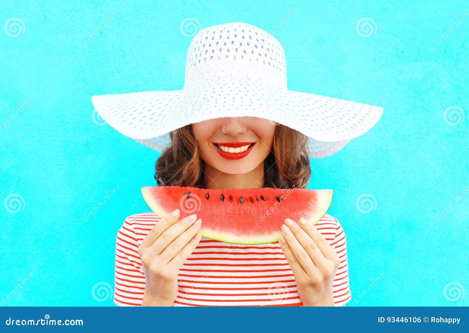 Glückliche lächelnde junge Frau des Modeporträts hält eine Scheibe der Wassermelone in einem Strohhut