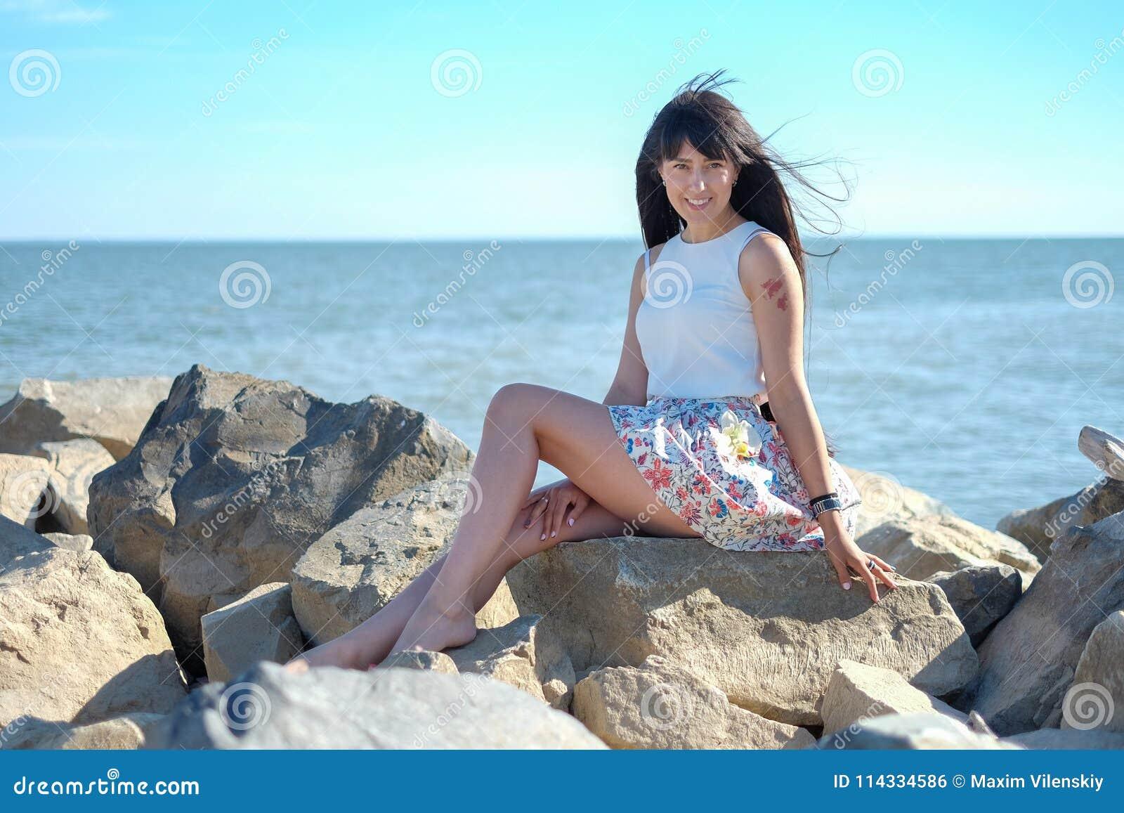 Glückliche lächelnde junge Frauen auf dem Seehintergrund