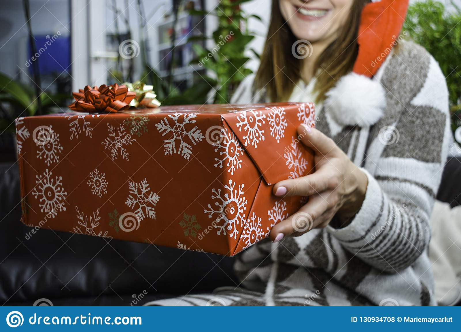 Glückliche lächelnde junge Schönheit, die ein Weihnachtsgeschenk hält und gibt