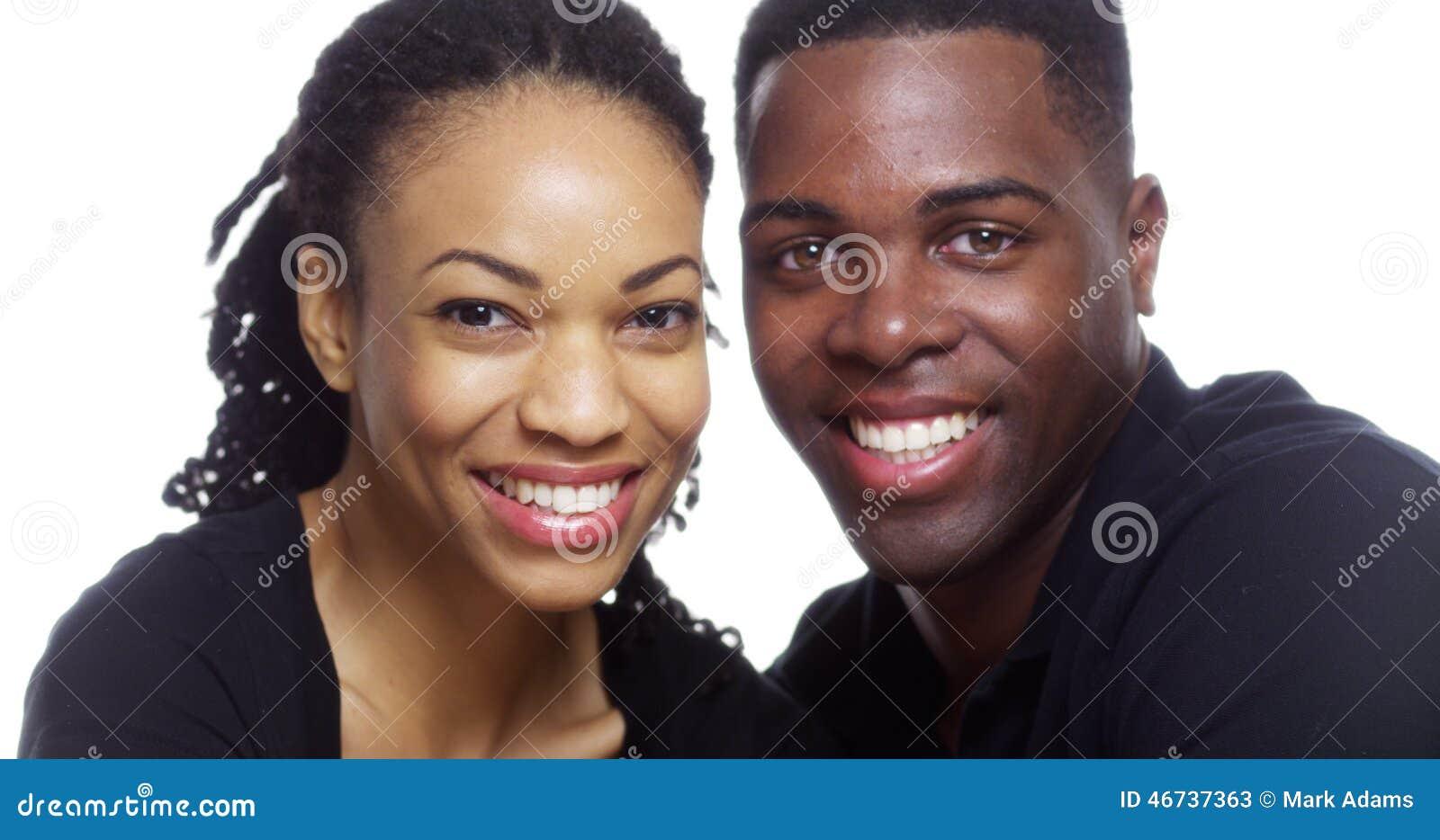 Glückliche lächelnde schwarze Paare, die Kamera auf weißem Hintergrund betrachten