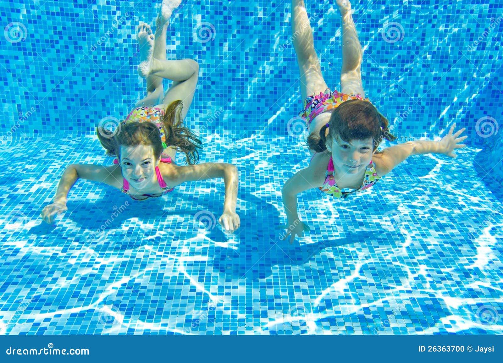 Glückliche lächelnde Unterwasserkinder im Swimmingpool