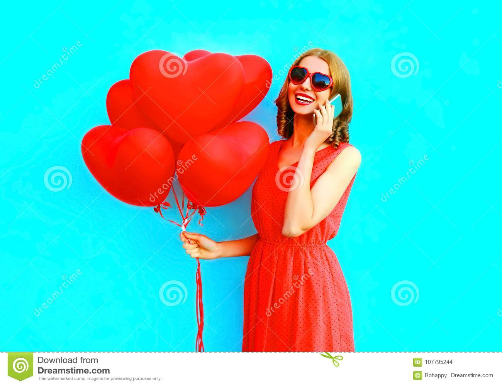 Glückliche lachende Frau des Porträts spricht am Telefon mit Ballonen einer Luft