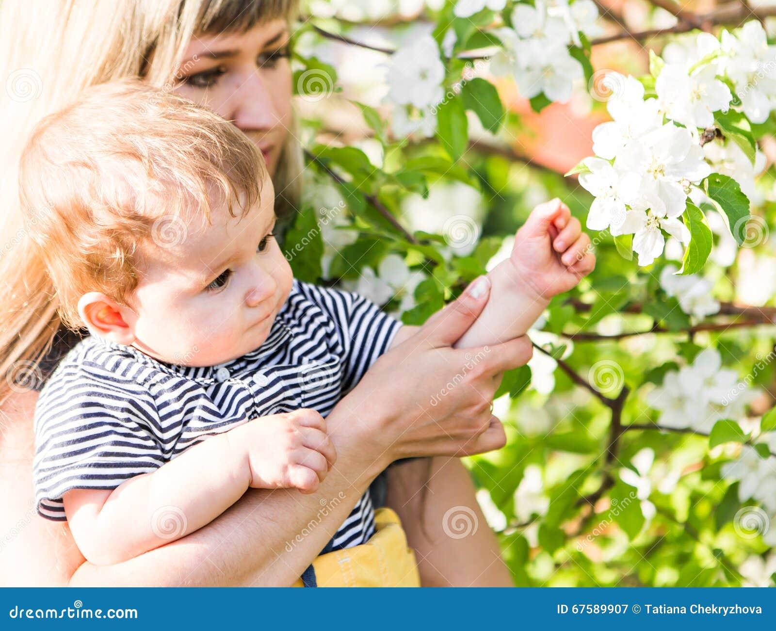 Glückliche liebevolle Familie mit Babysohn in blühendem Frühlingsgarten Bemuttern Sie Holdingschätzchen Die Zeit zusammen verbrin