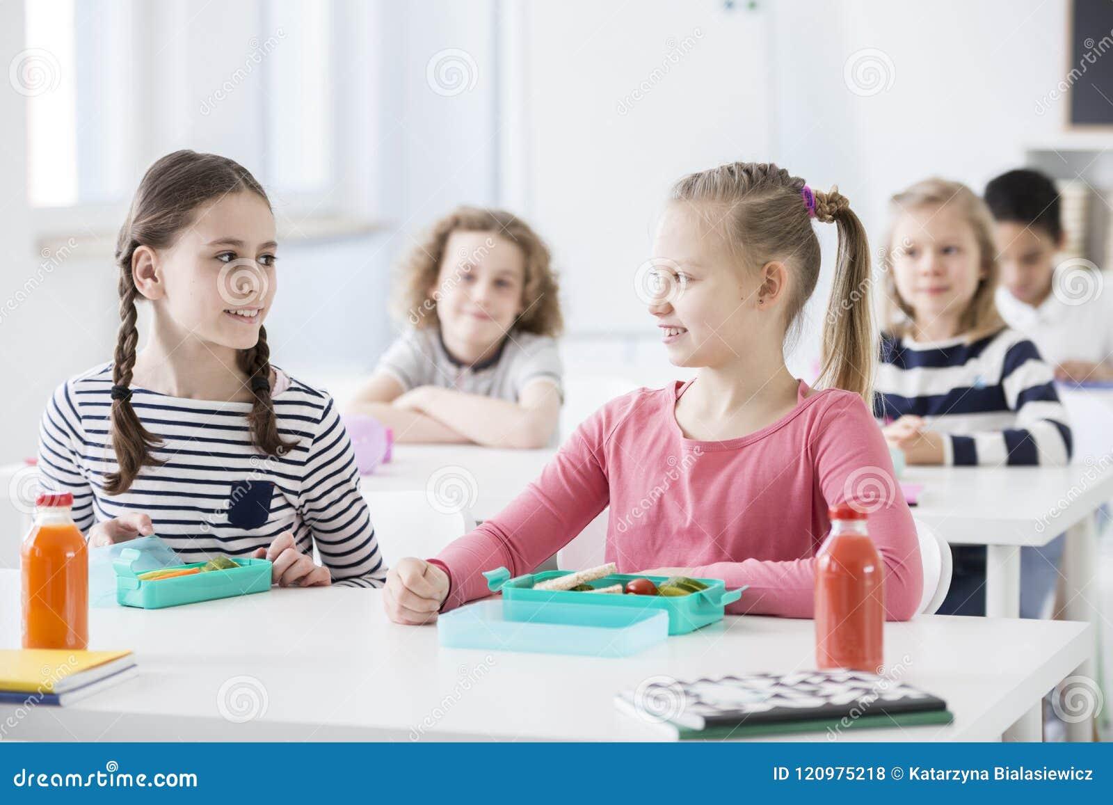 Glückliche Mädchen, die in der Schule Bruch genießen und Frühstück essen