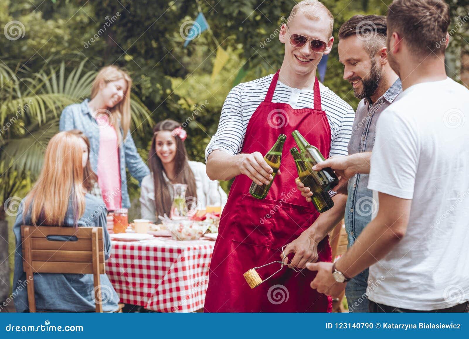 Glückliche Männer, die während des Gartenfests mit Freunden zujubeln