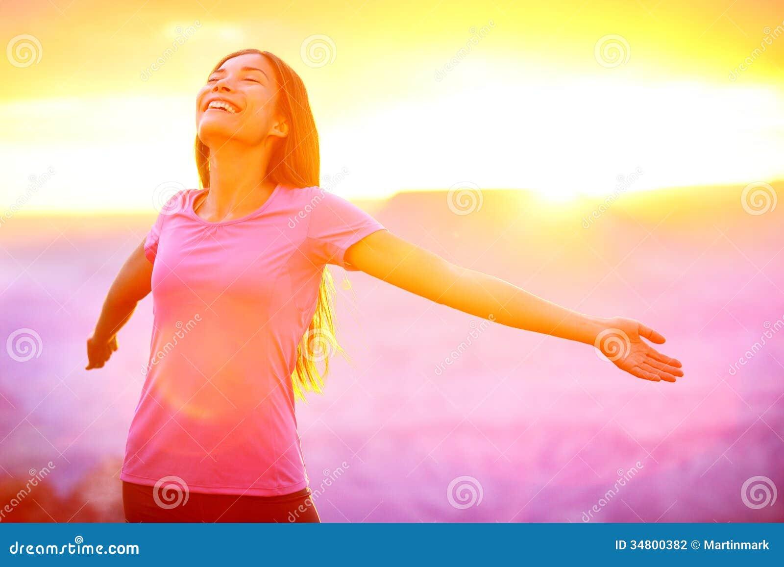 Glückliche Menschen - freie Frau, die Natursonnenuntergang genießt