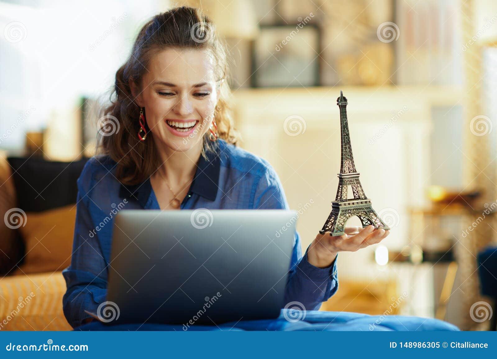 Gl?ckliche moderne Frau mit Andenken des Eiffelturms unter Verwendung des Laptops