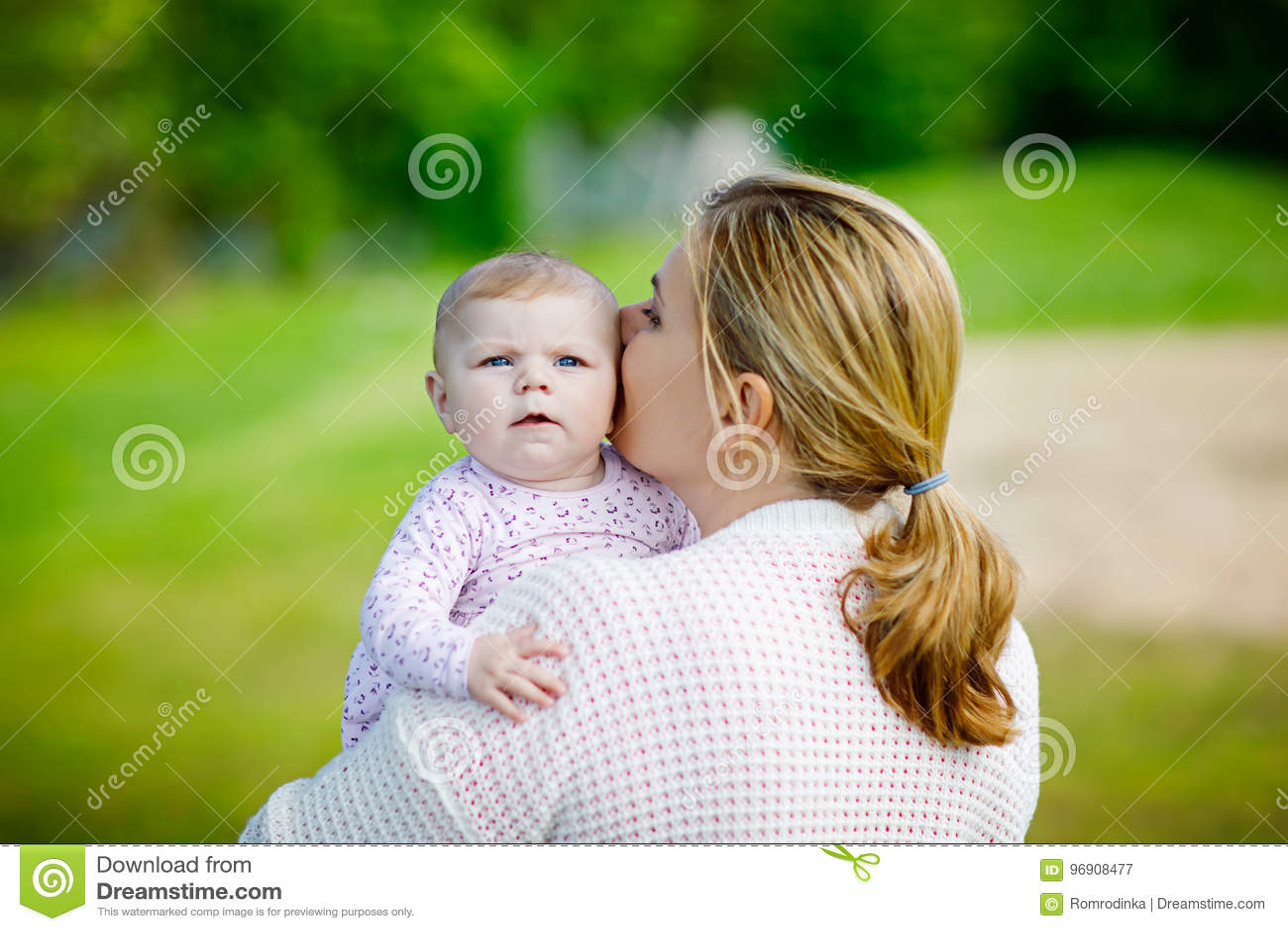 Glückliche Mutter, die Spaß mit neugeborener Babytochter draußen hat