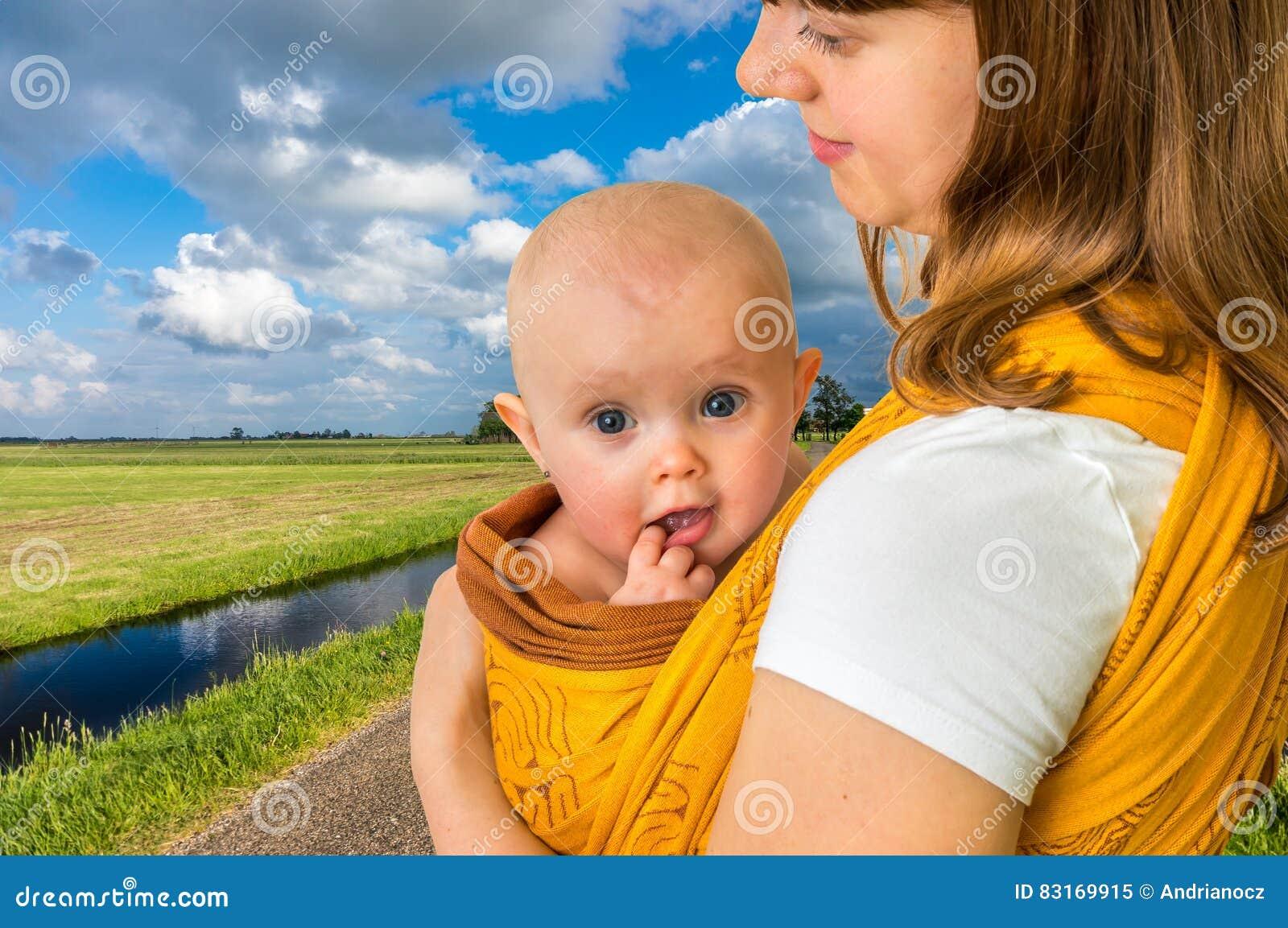 Glückliche Mutter mit ihrem Baby in einem Riemen