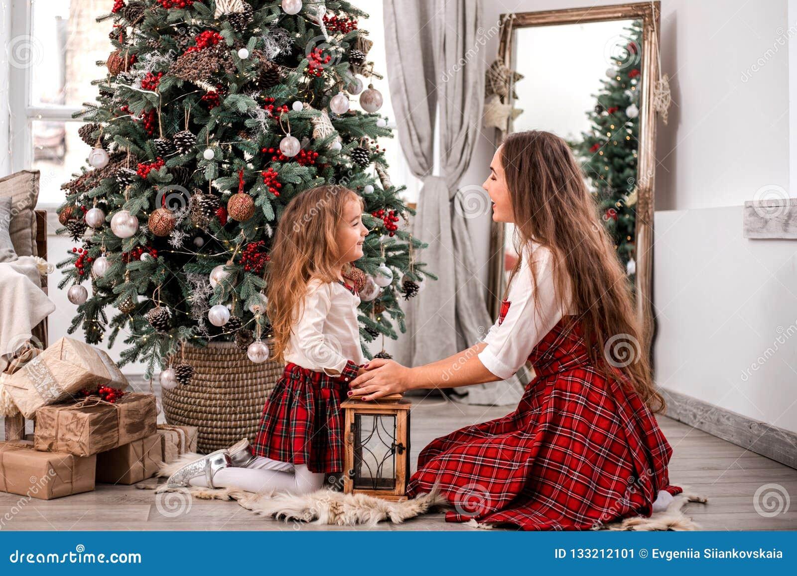 Glückliche Mutter- und Tochtersitzplätze nahe Tannenbaum