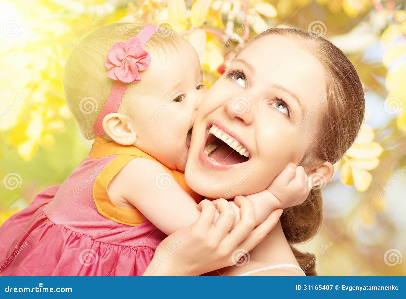 Glückliche nette Familie. Mutter und Baby, die in der Natur im Freien küsst