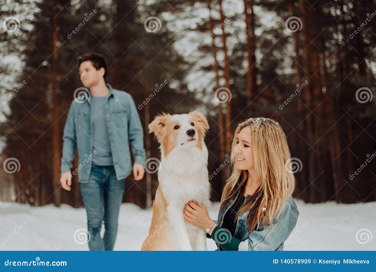 Glückliche nette lächelnde Paare von jungen Leuten in den Denimklagen im schneebedeckten Wald im Winter mit rotem Hund border col