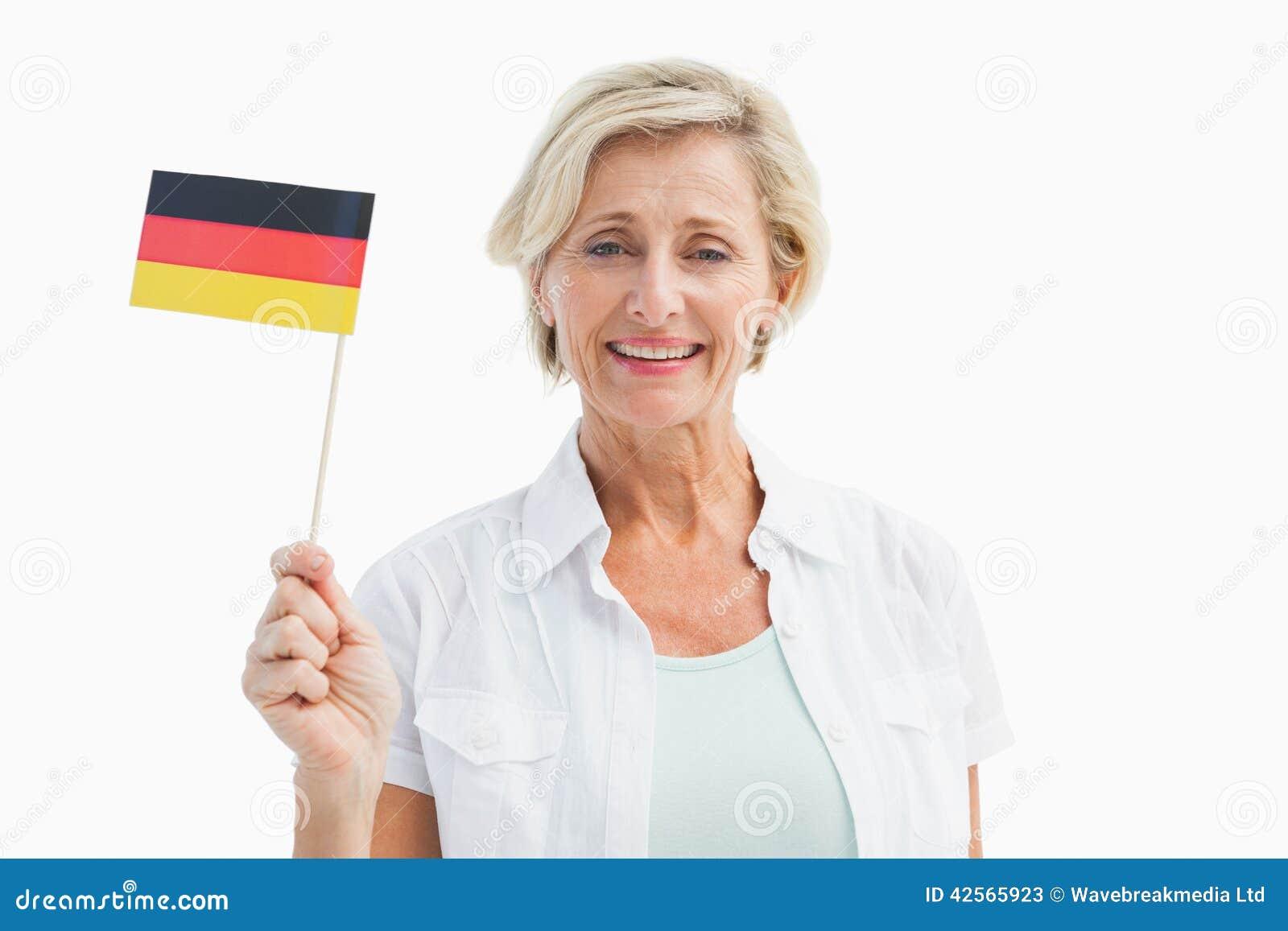 Glückliche reife Frau, die deutsche Flagge hält