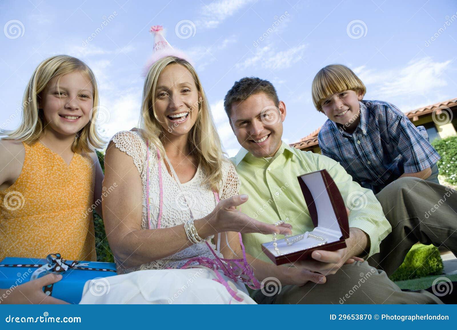 Glückliche reife Frau, die mit Familie sitzt
