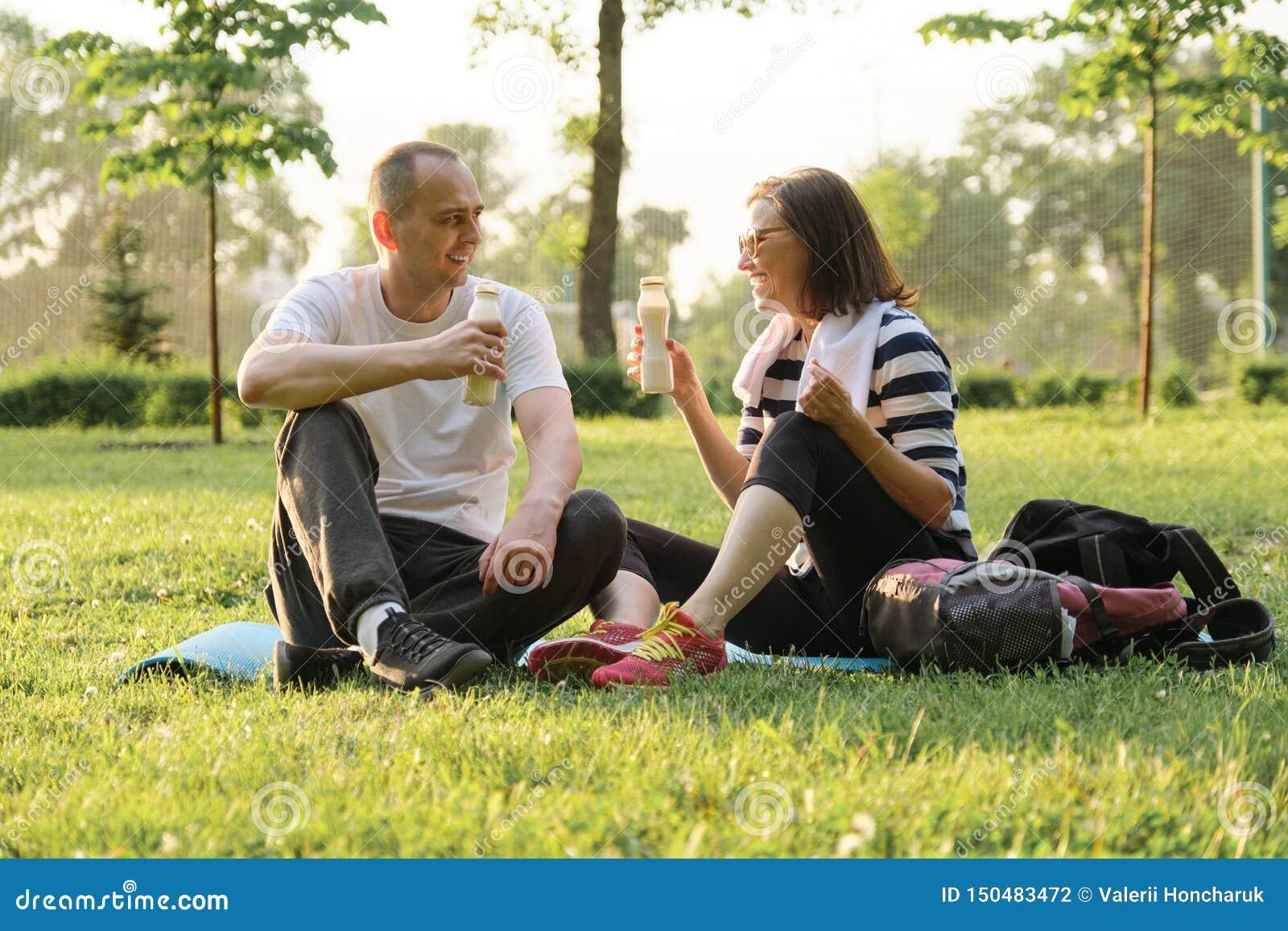 Glückliche reife Paare, die im Park auf Eignungsmatte, stillstehender trinkender Jogurt nach Sportübungen sitzen