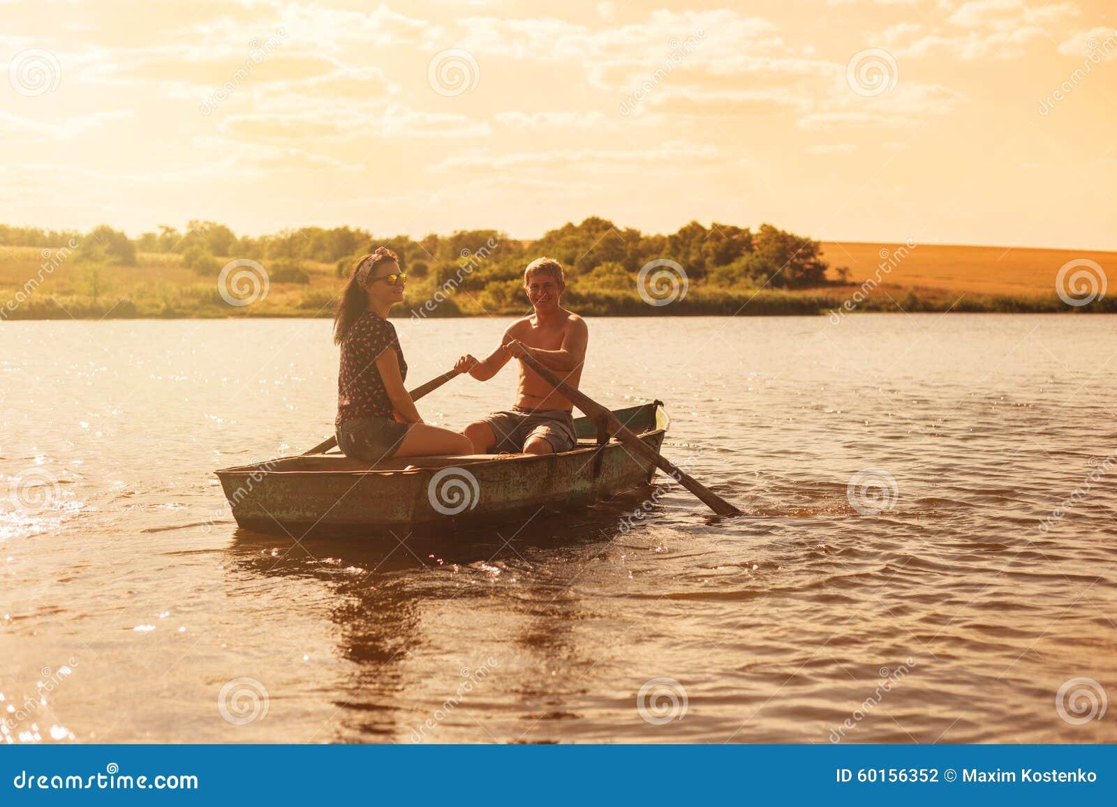 Glückliche romantische Paare, die ein Boot rudern