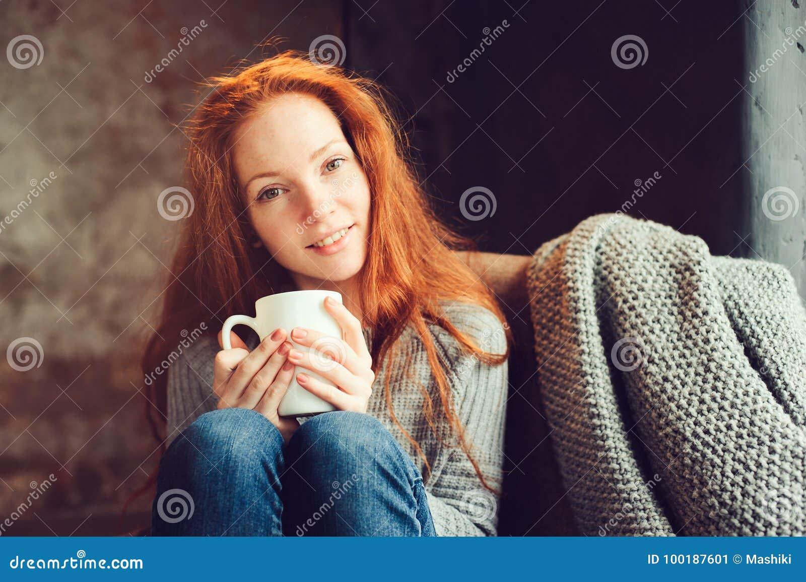 Glückliche Rothaarigefrau, die sich zu Hause im gemütlichen Winter- oder Herbstwochenende mit dem Buch und Schale heißem Tee, sit