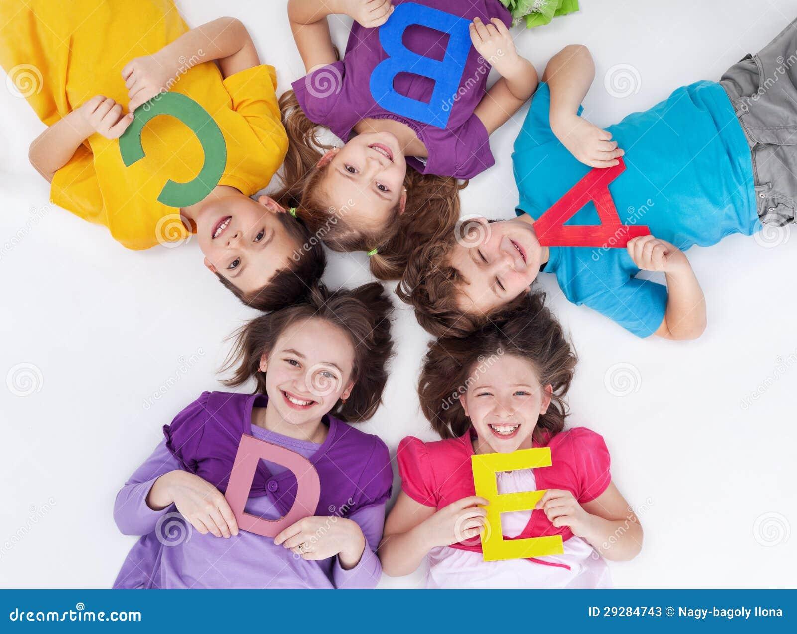 Glückliche Schulkinder mit bunten Alphabetzeichen