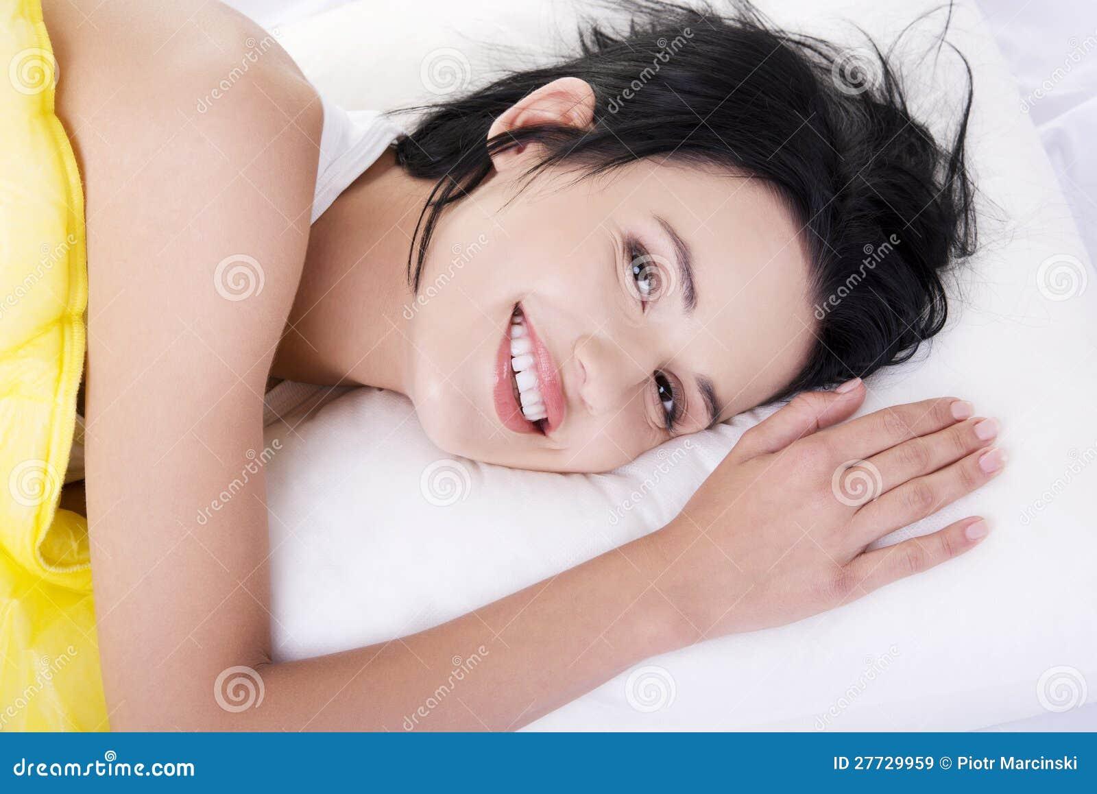 Glückliche sinnliche junge Frau, die im Bett liegt