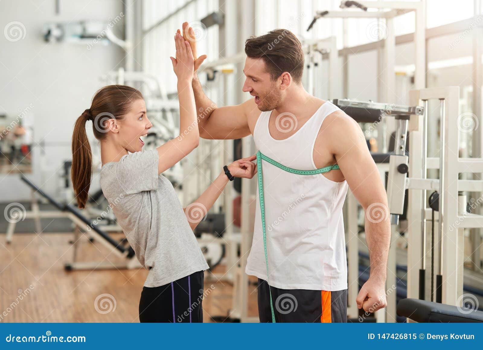 Glückliche sportliche Paare, die miteinander hohe fünf geben