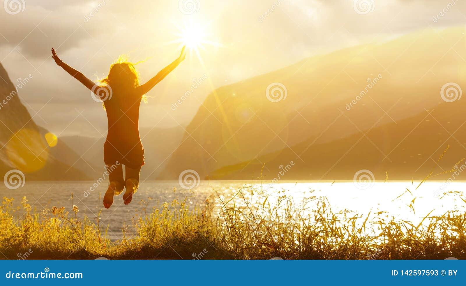 Glückliche springende Frau an einem See