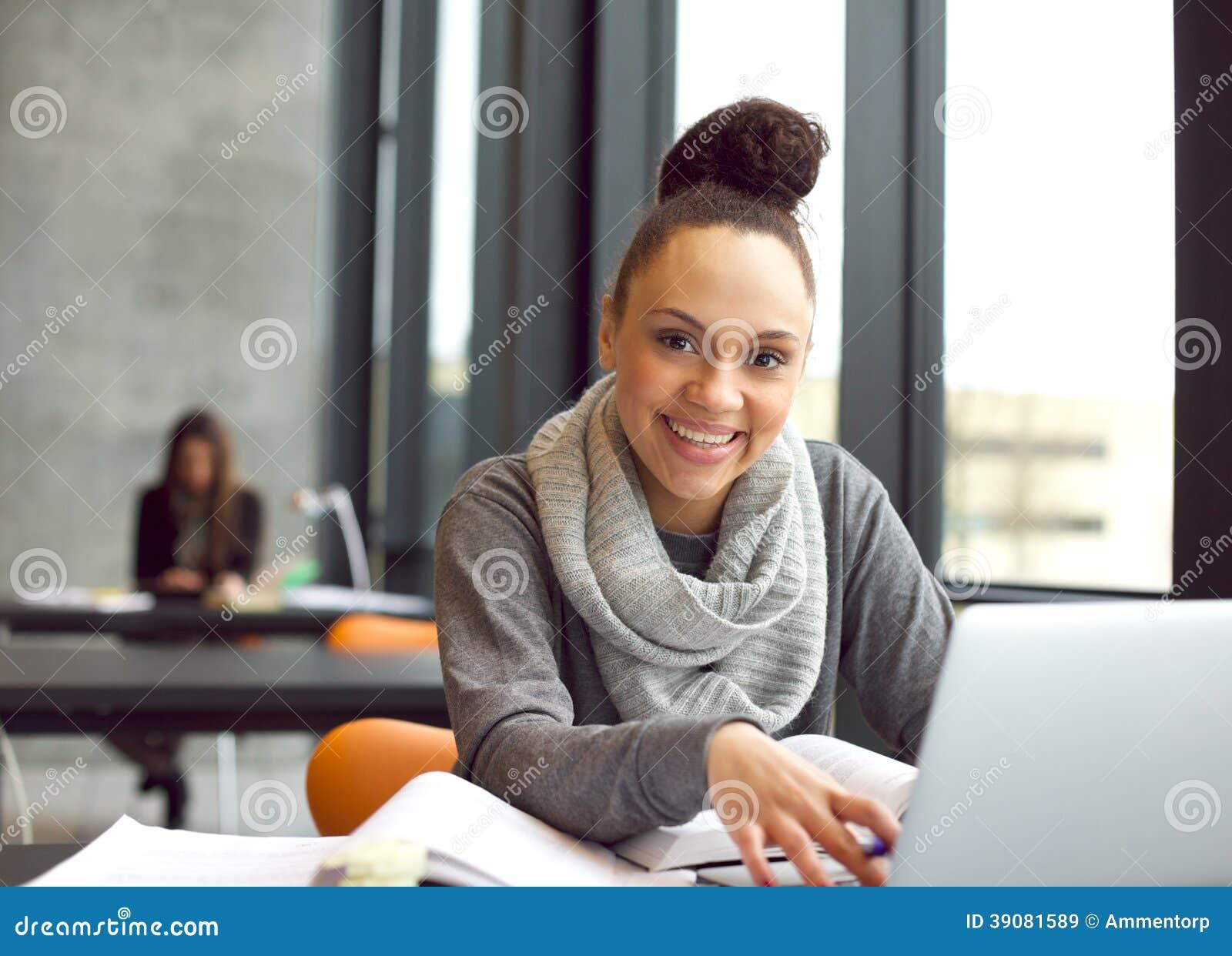 Glückliche Studien der jungen Frau in der Bibliothek