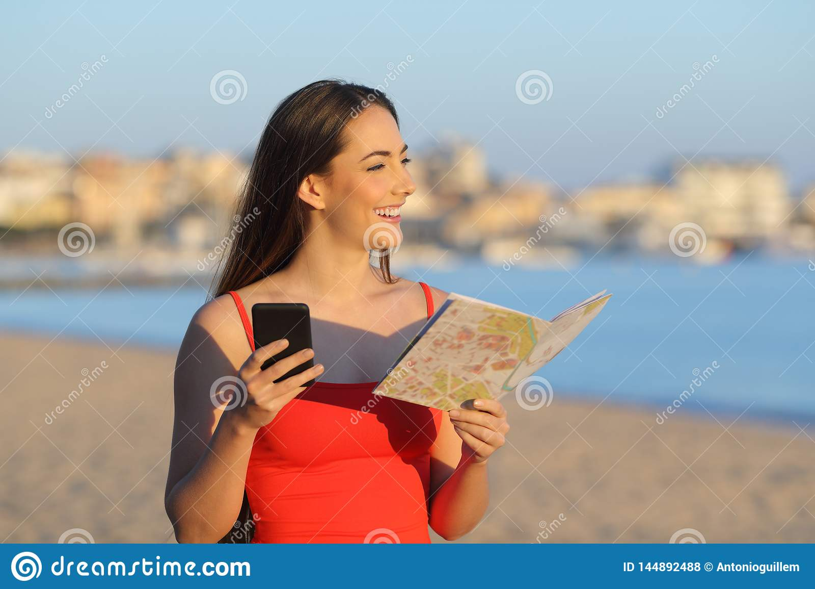 Glückliche touristische haltene Karte und Telefon, die den Strand erwägt