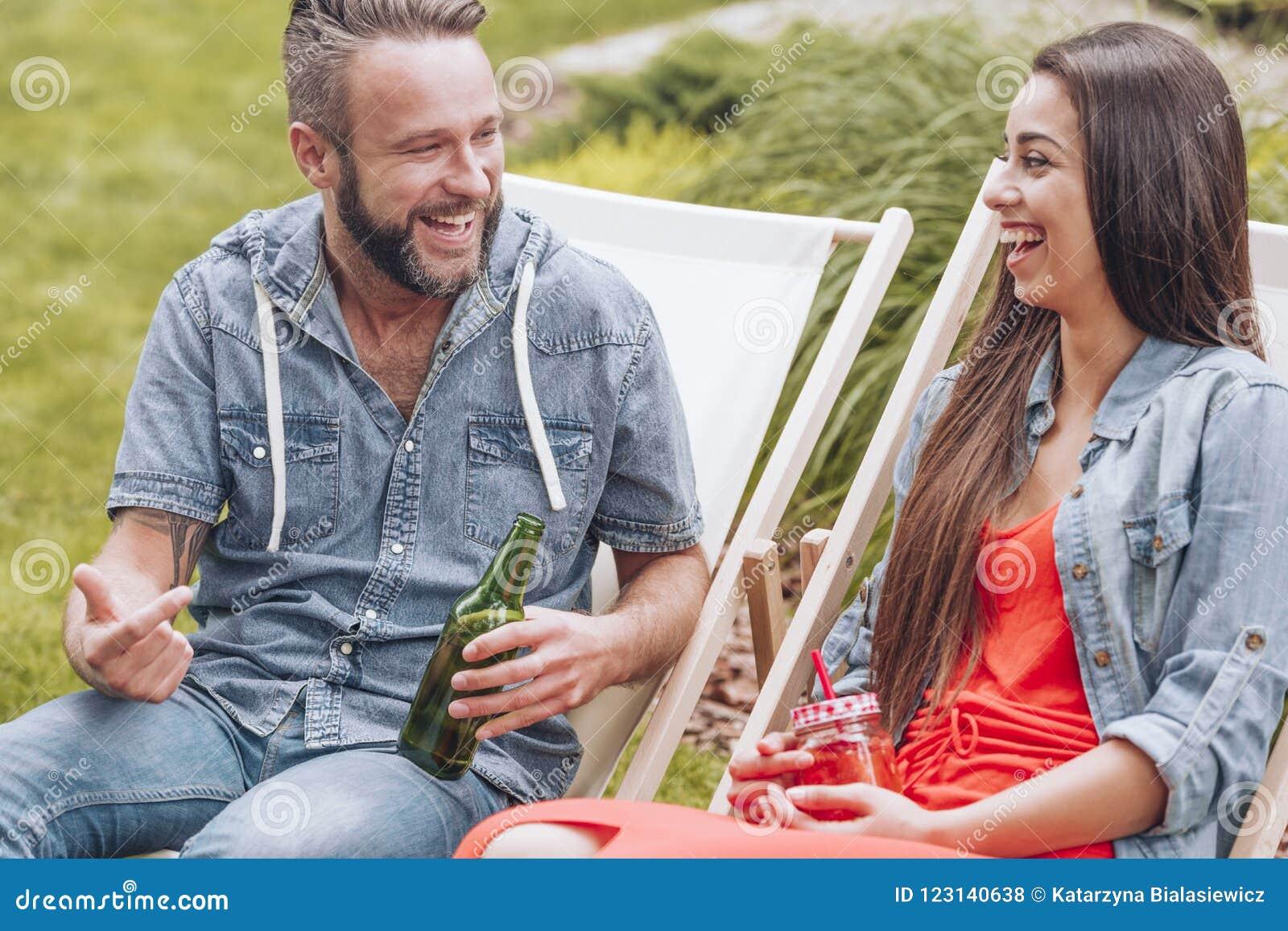 Glückliche und lächelnde Paare, die das Treffen während Partei der im Freien genießen