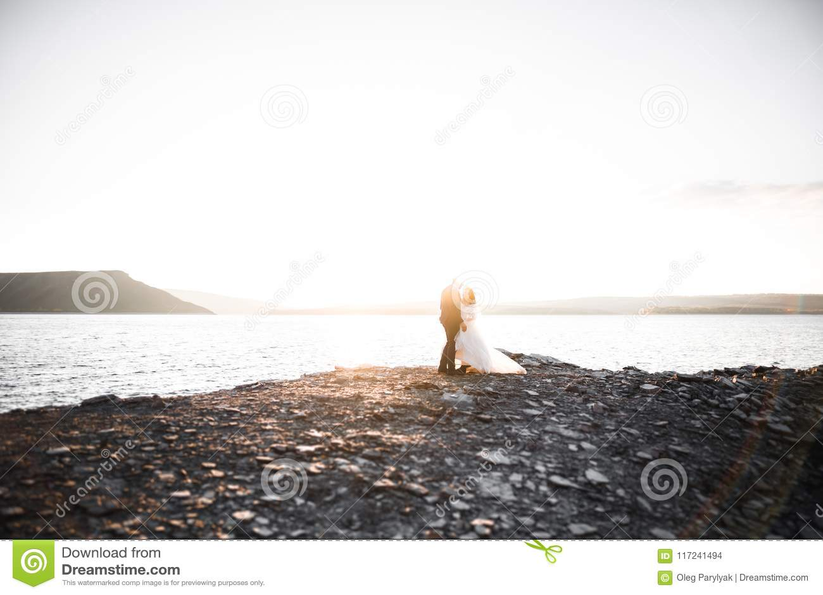 Glückliche und romantische Szene gerade von den verheirateten jungen Hochzeitspaaren, die auf schönem Strand aufwerfen