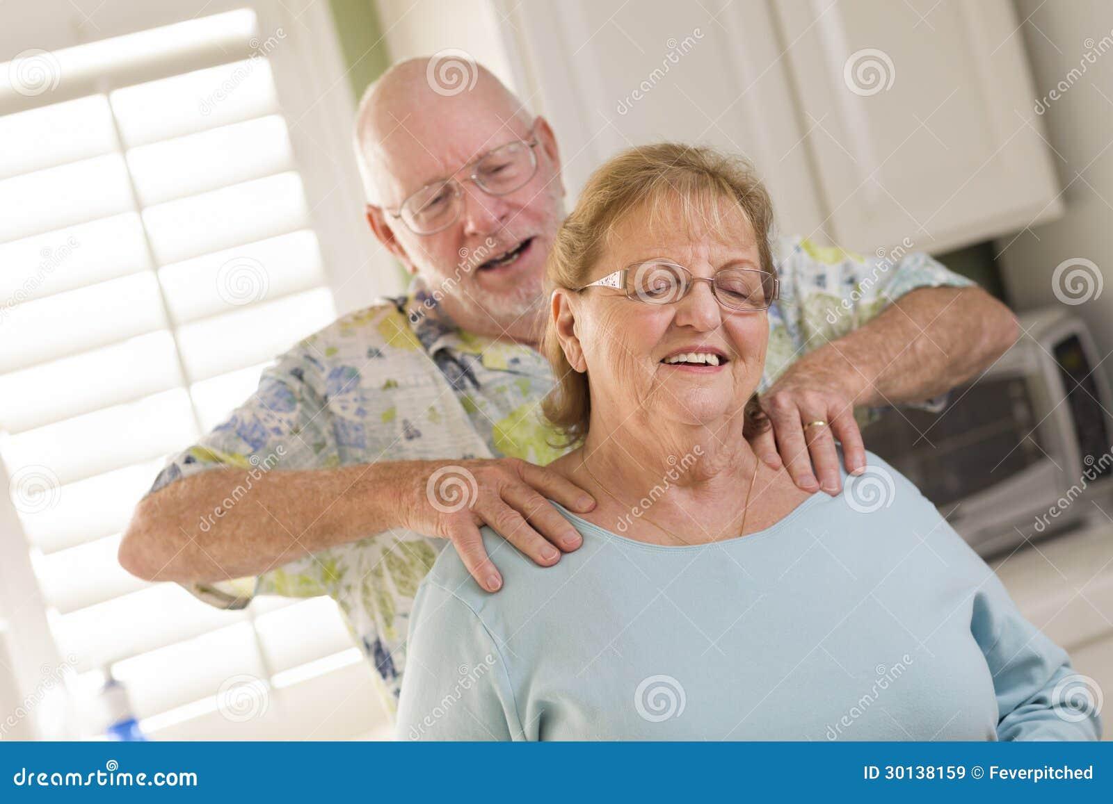 Älterer erwachsener Ehemann, der Frau eine Schulter-Unebenheit gibt