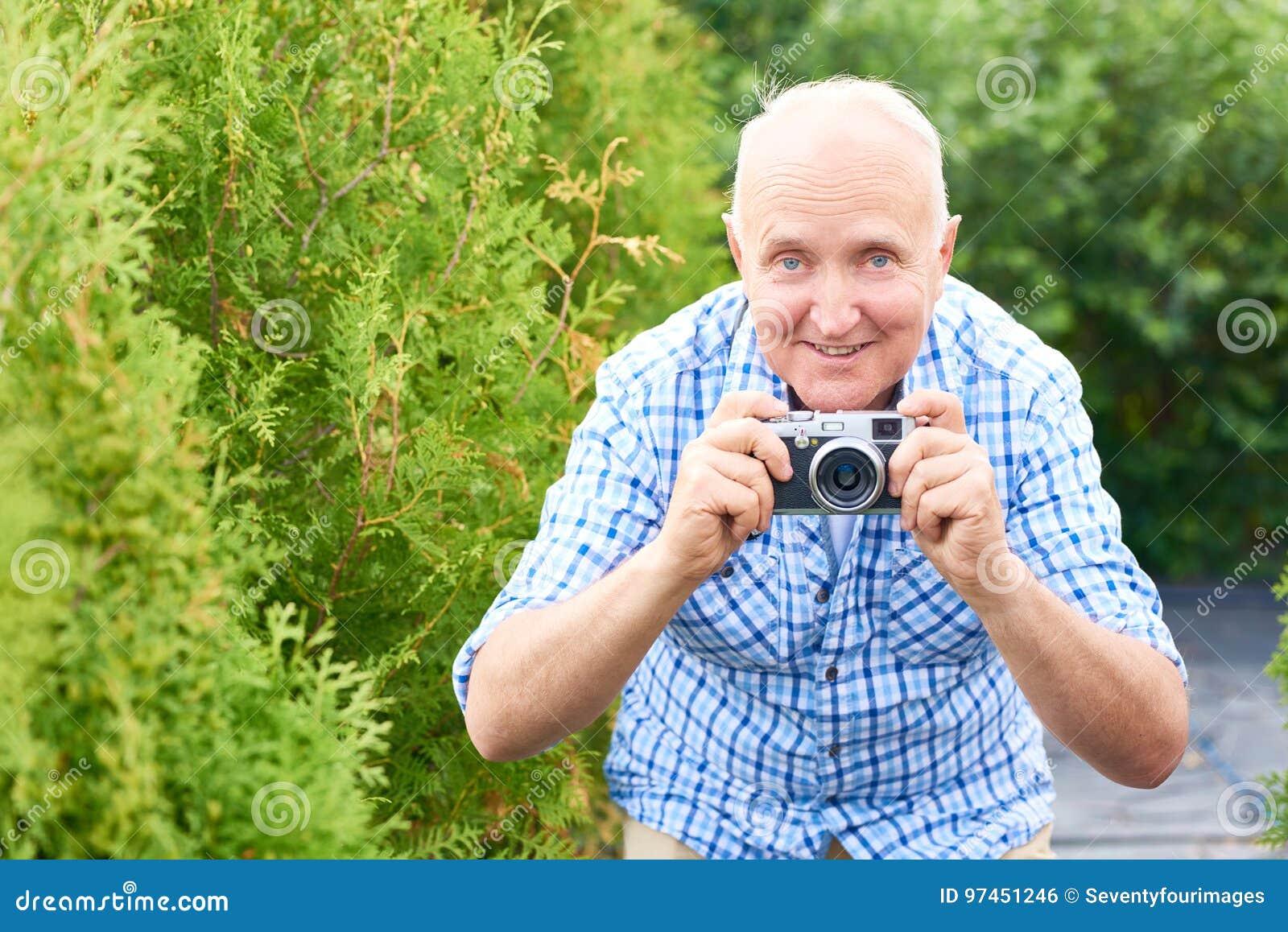 Glücklicher älterer Mann, der Fotos im Park macht