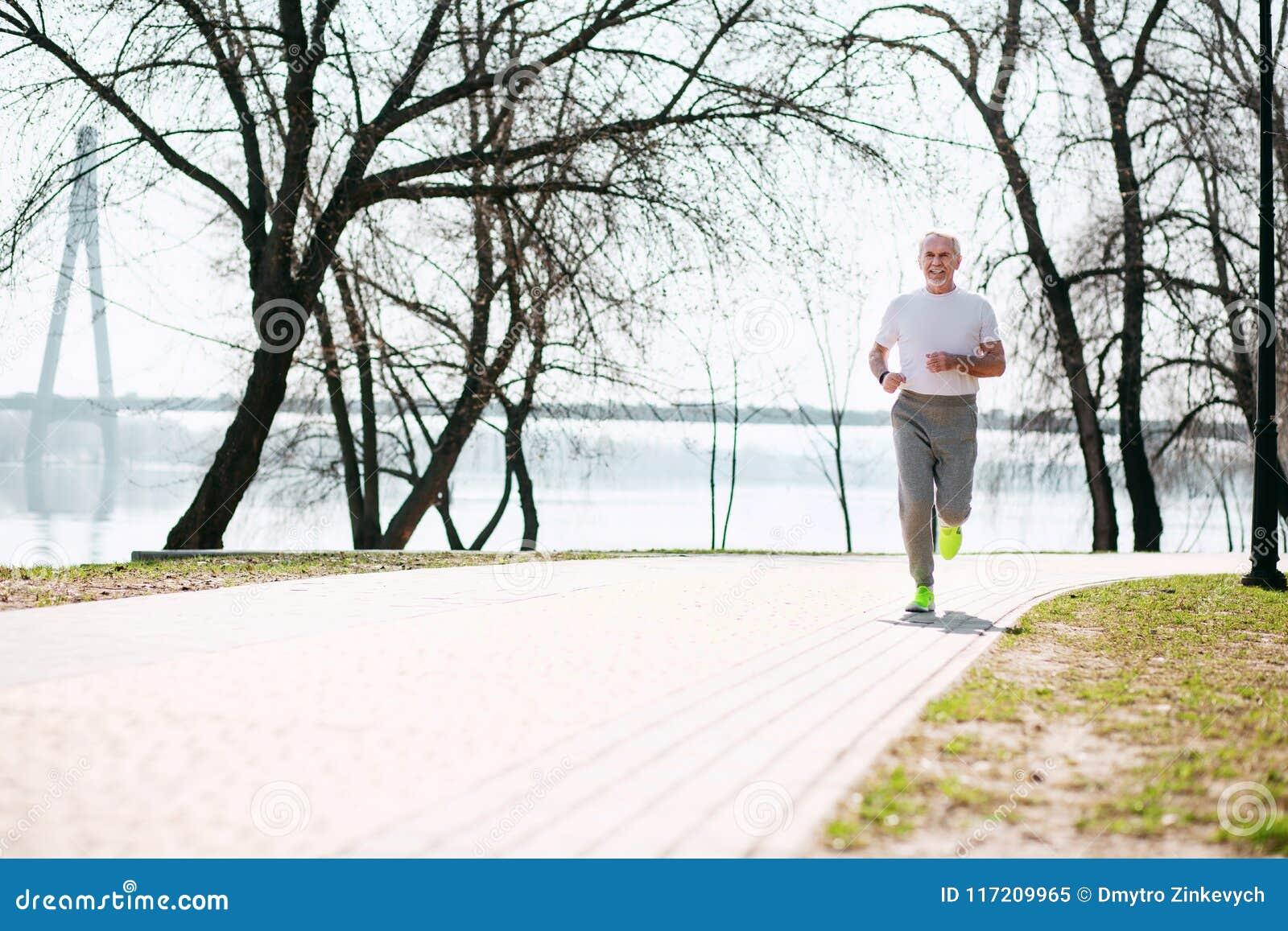 Glücklicher älterer Mann, der in Park läuft