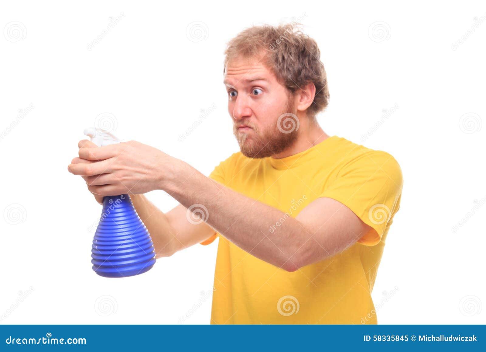Glücklicher bärtiger Mann wäscht sich mit Spray und Gummi
