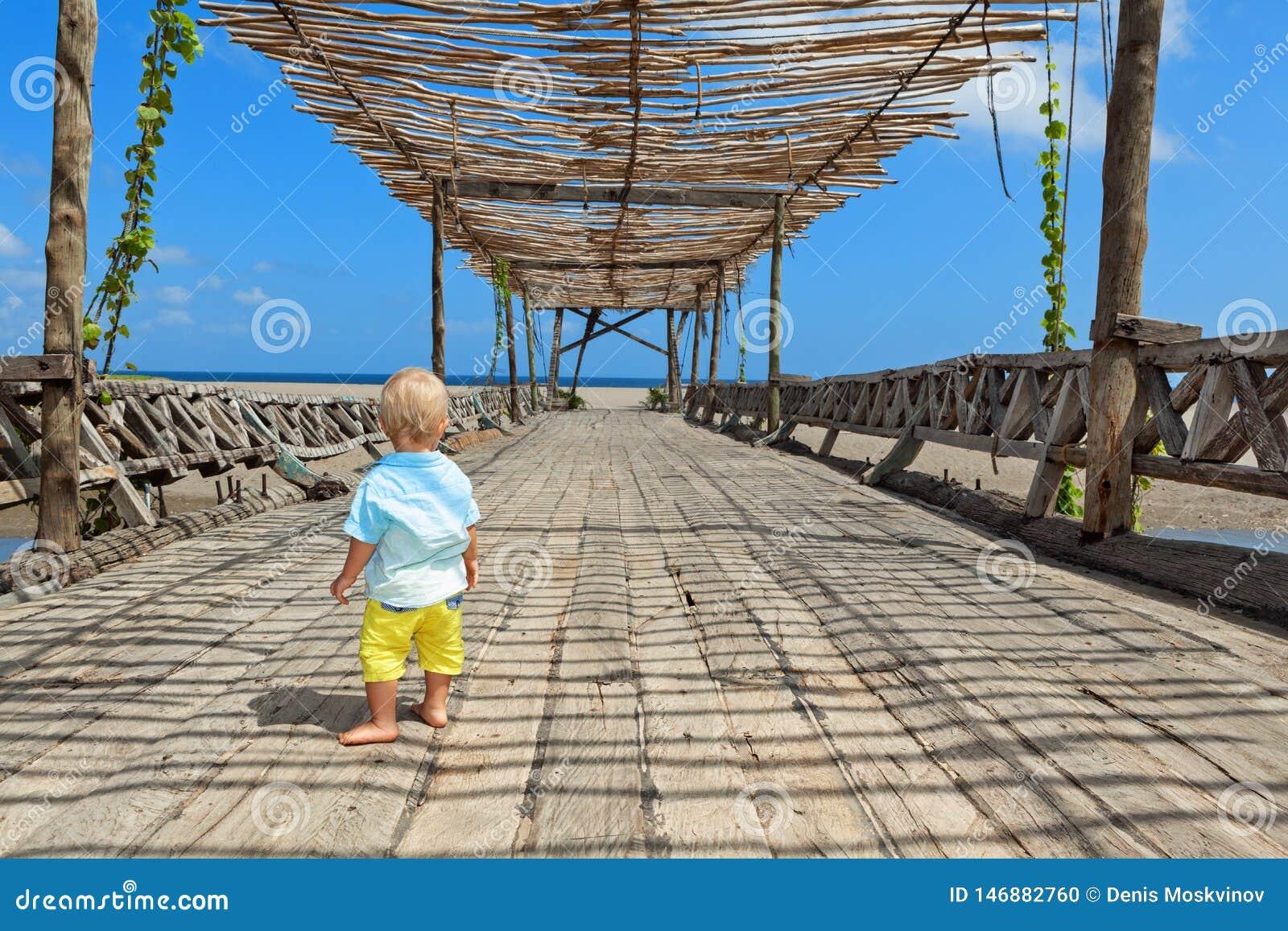 Glücklicher Babyweg durch hölzerne Brücke zum Ozeanstrand