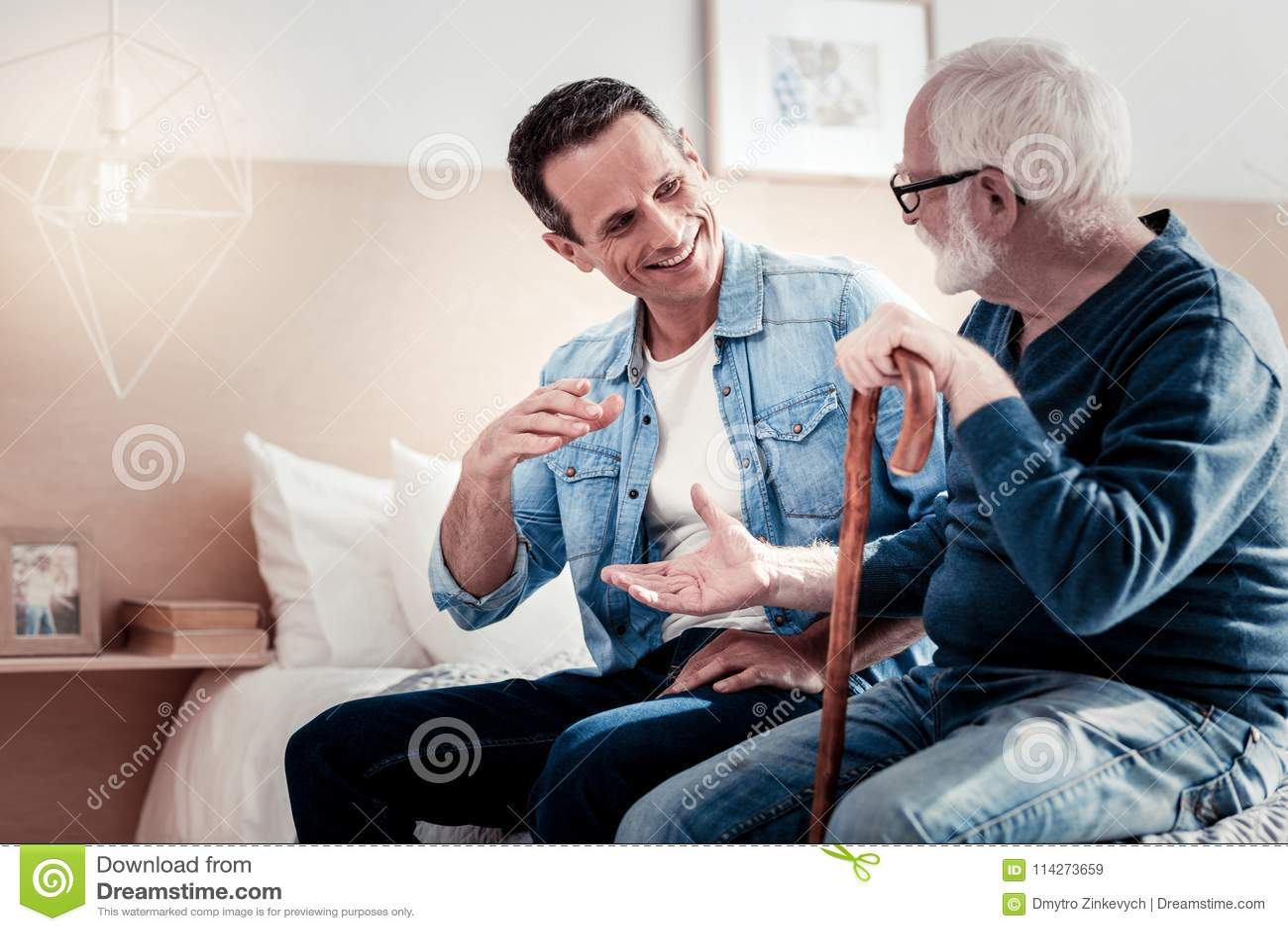 Glücklicher begeisterter Vater und Sohn, welche die Fotos betrachtet