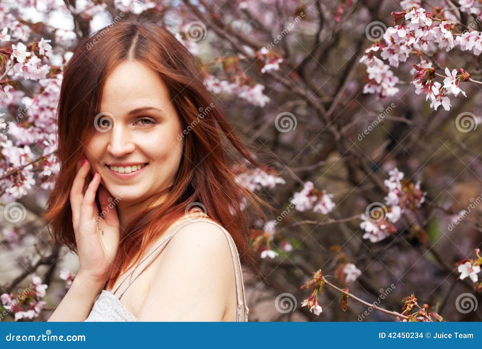 Glücklicher Blumengarten der jungen Frau im Frühjahr