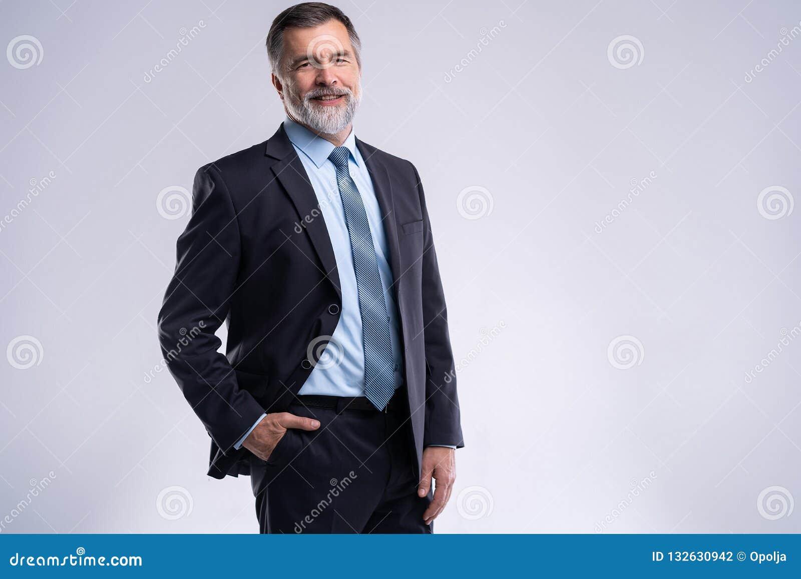Glücklicher erfüllter reifer Geschäftsmann, der die Kamera lokalisiert auf weißem Hintergrund betrachtet