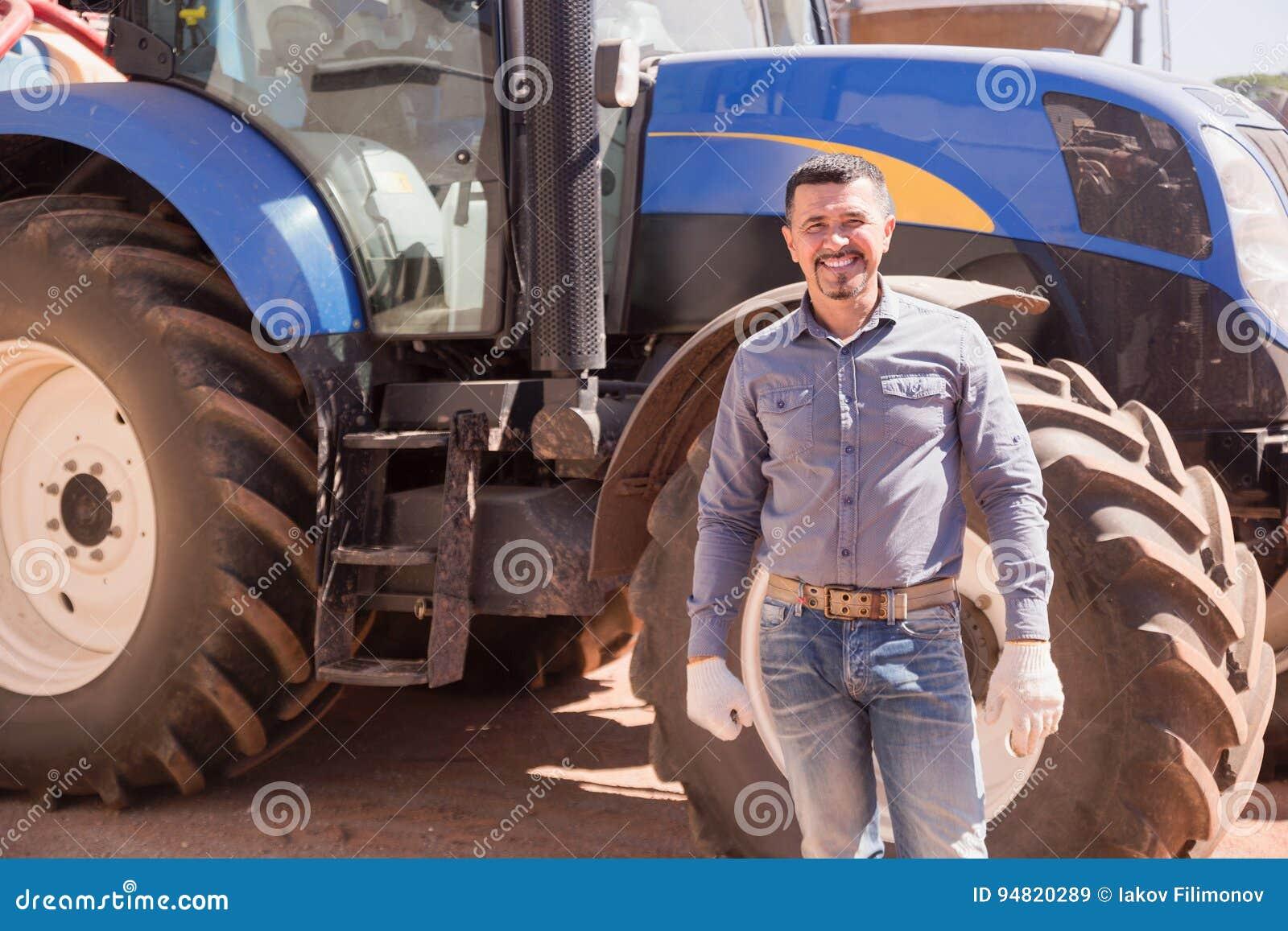 Glücklicher Fahrerlandwirt, der mit großem Traktor steht