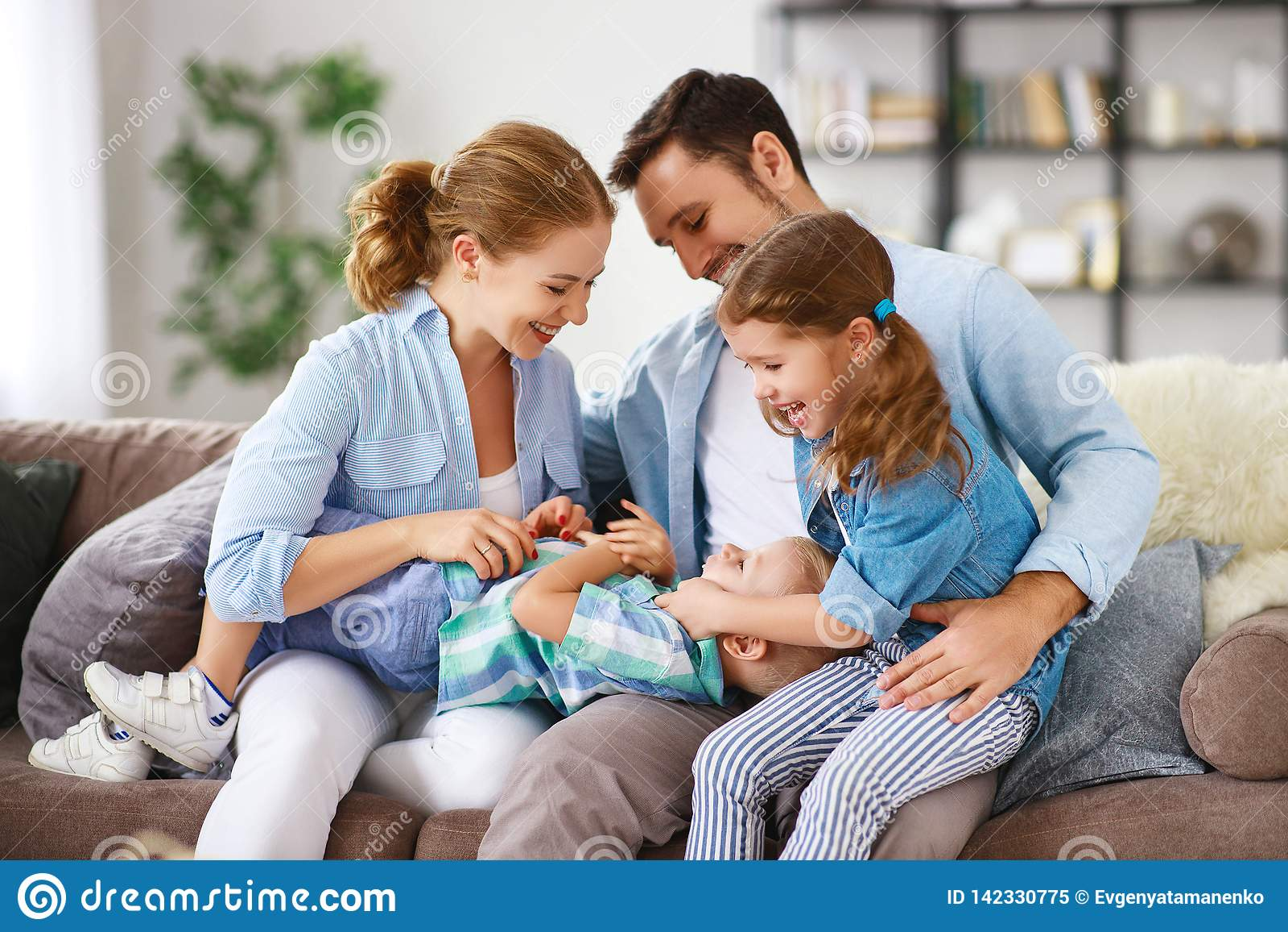 Glücklicher Familienmuttervater und -kinder zu Hause auf Couch