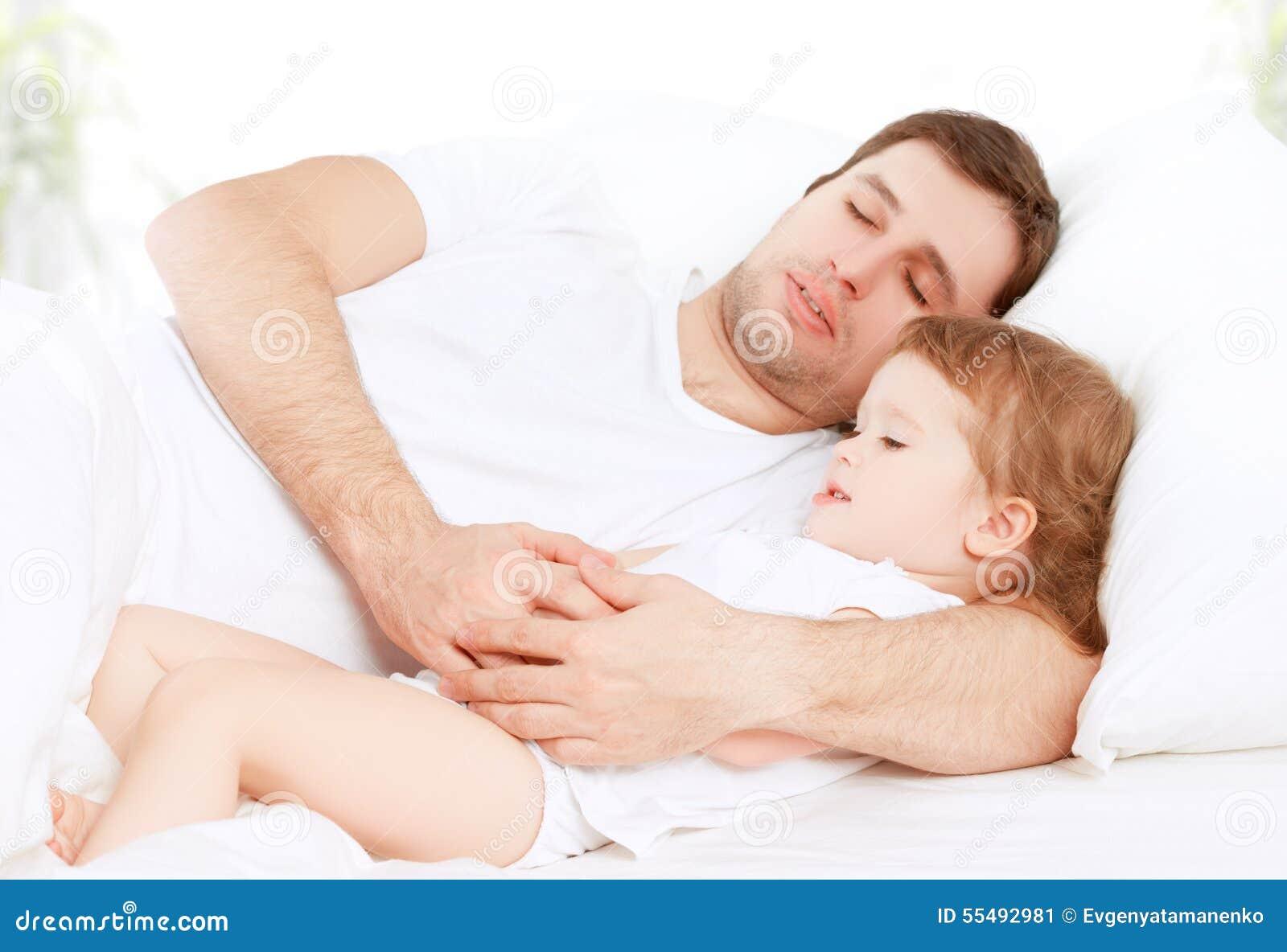 Glücklicher Familienvater und Kinderbabytochter, die im Bett schläft