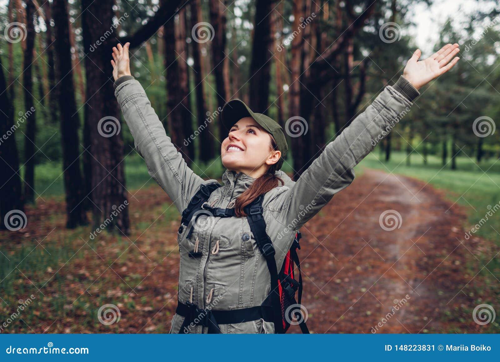 Glücklicher Frauentourist, der im Frühjahr Wald geht und die Arme frei glauben anhebt Reisen und Tourismuskonzept
