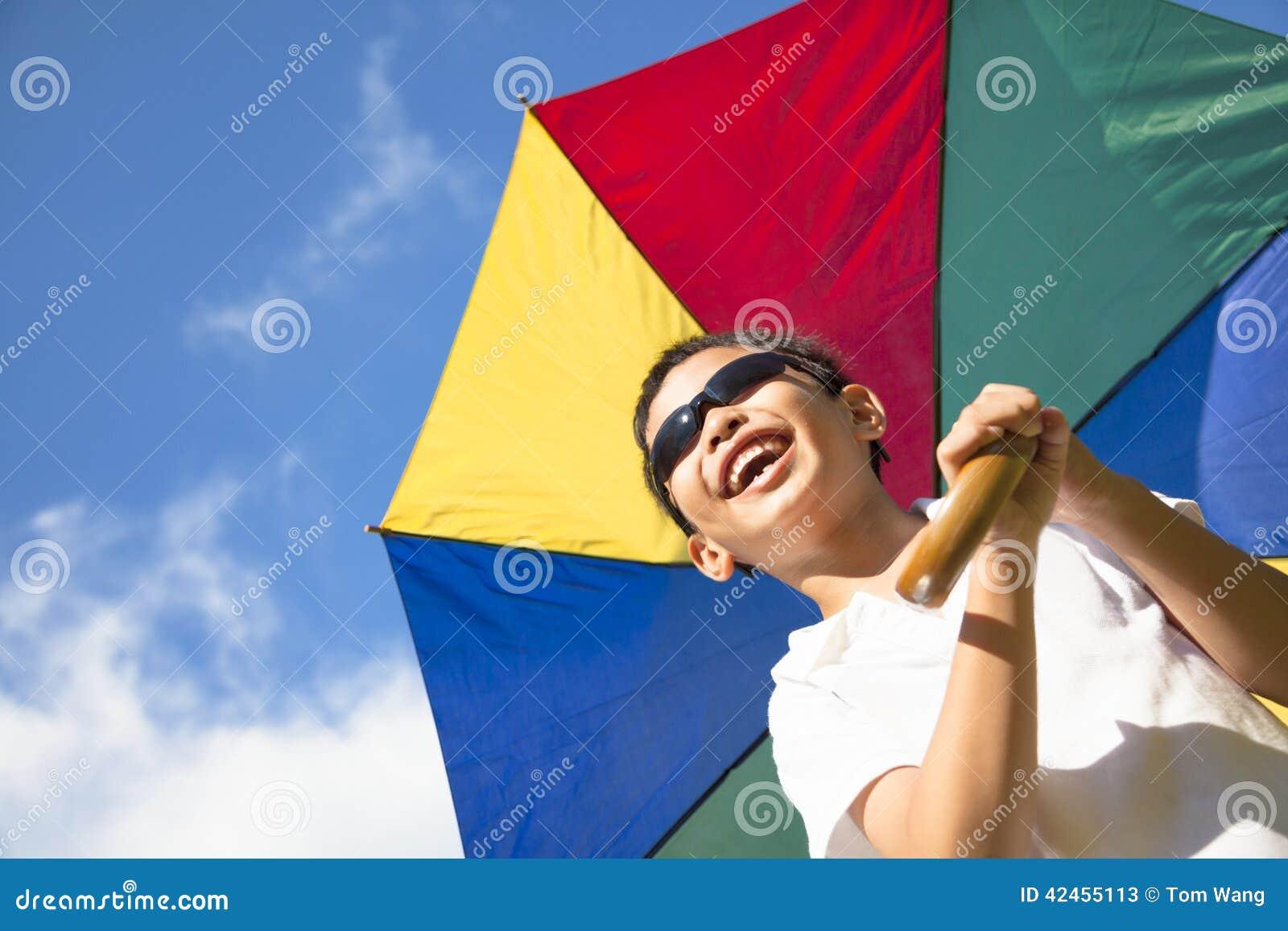 Glücklicher Griff des kleinen Jungen ein bunter Regenschirm