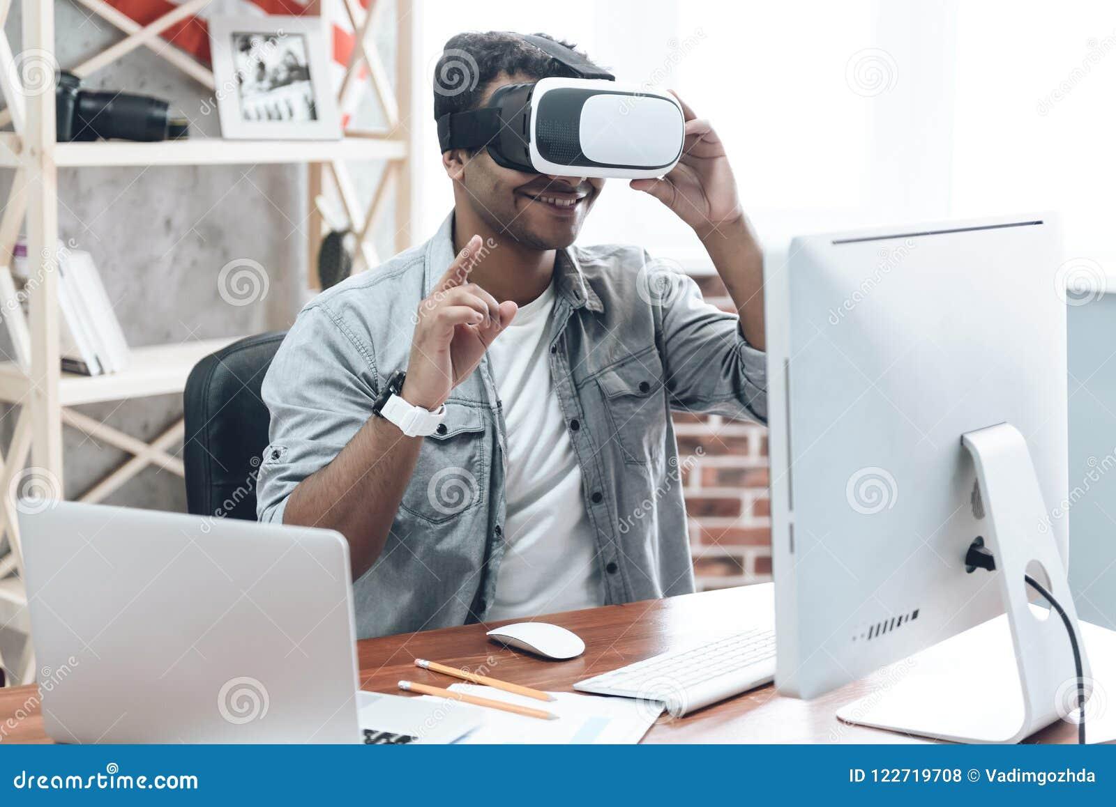 Glücklicher indischer junger Mann zu Hause in VR-Gläsern