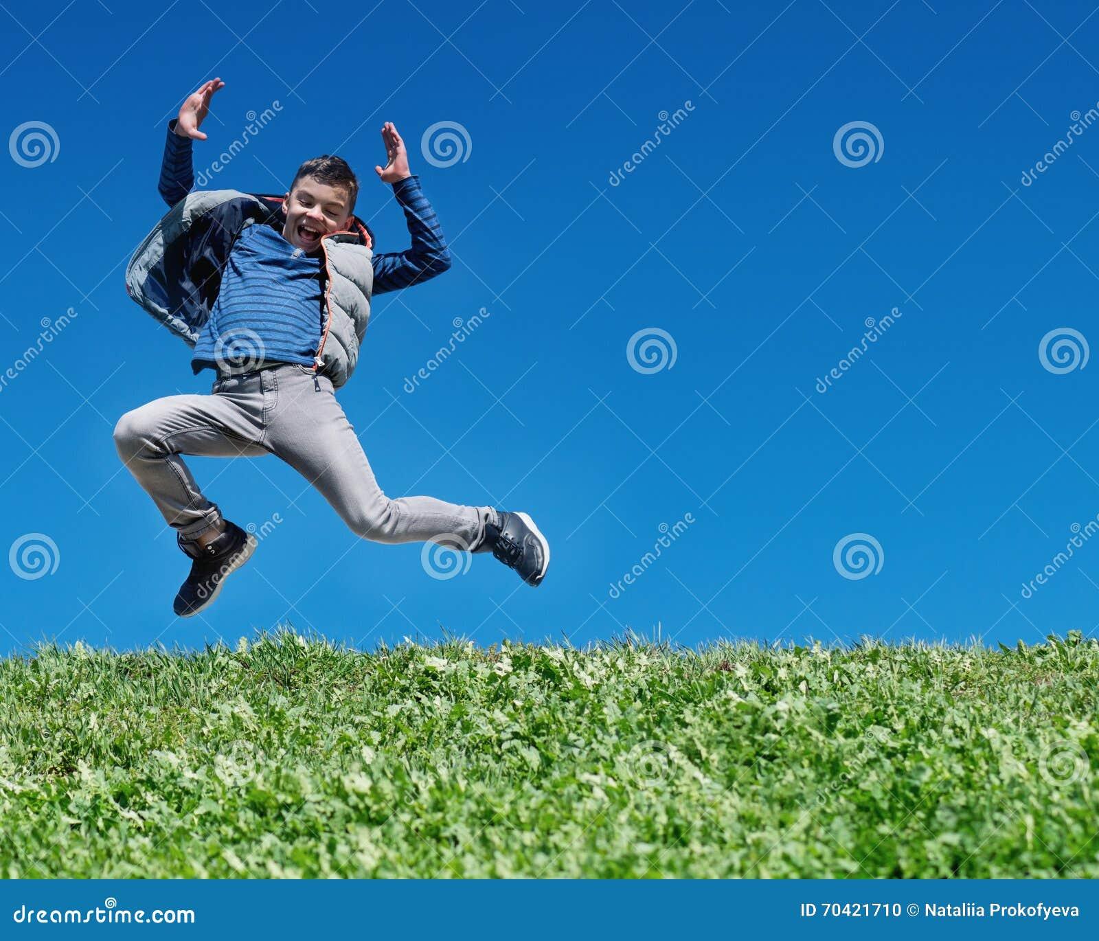 Glücklicher jugendlich Junge, der auf Wiese springt