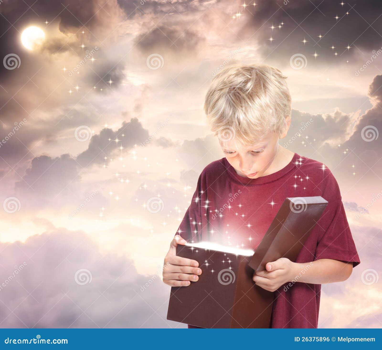 Glücklicher Junge, der einen Geschenk-Kasten öffnet