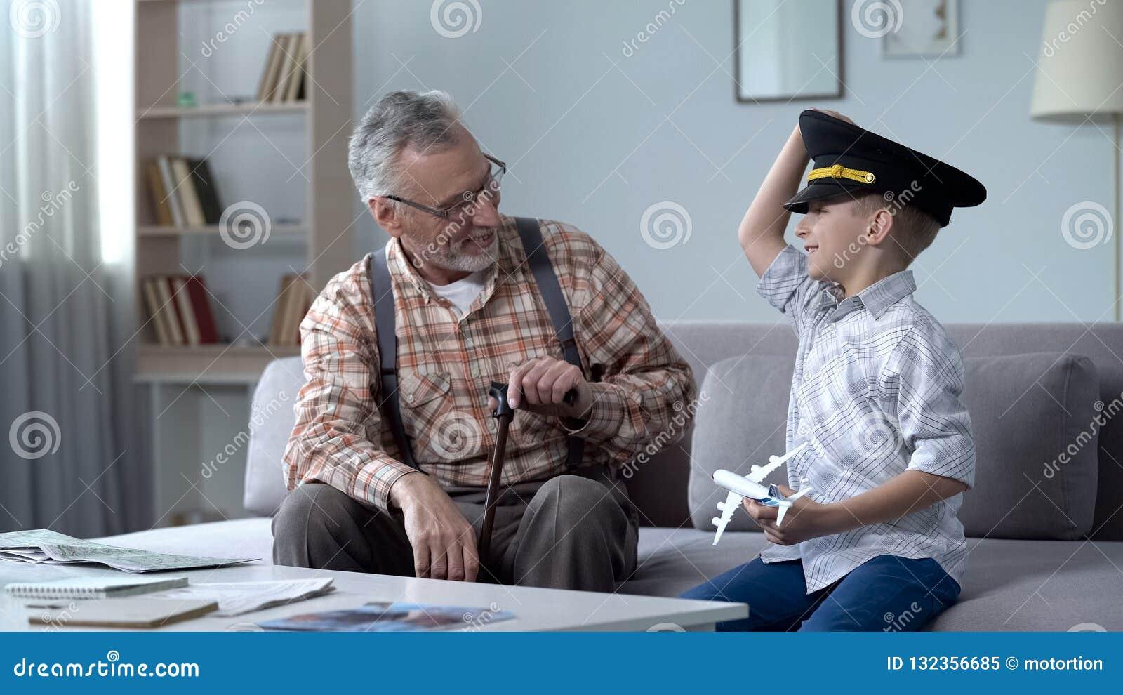 Glücklicher Junge, der mit Spielzeugflugzeug, großväterlicher ehemaliger Pilot stolz auf Enkel spielt